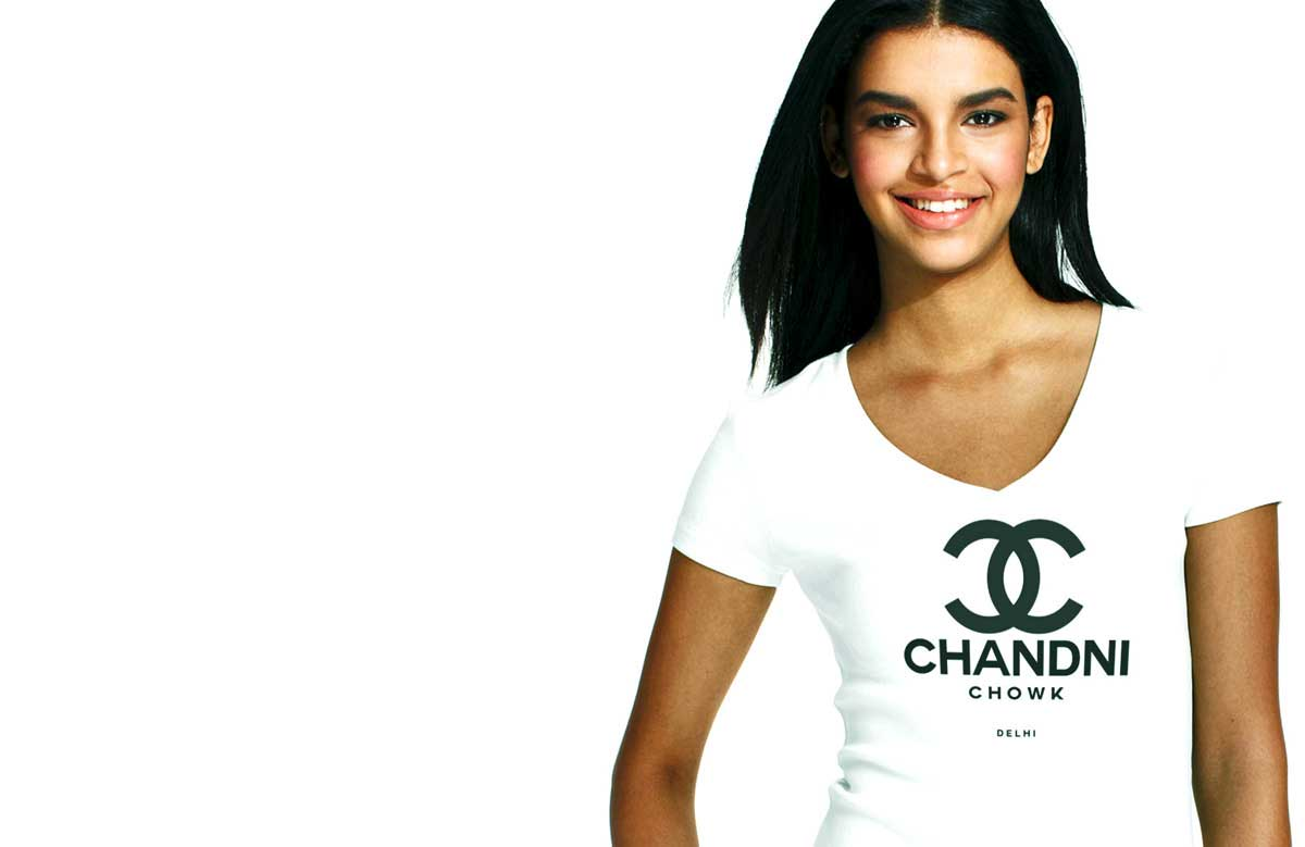 South Asian model wearing Gildan SoftStyle V Neck tshirt with black silkscreened image on front that says Chandhni Chowk. Tshirt is designed by Brown Man Clothing Co.